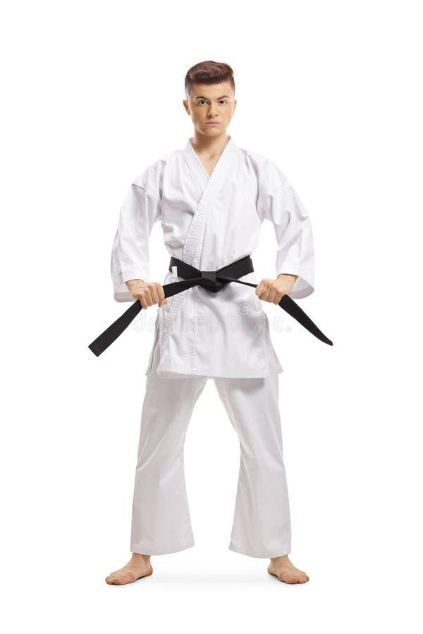 Teenage boy in karate kimono holding his black belt royalty free stock image
