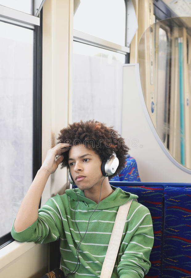 Teenage Boy Listening Music In Train. Young teenage boy listening music with headphones in commuter train stock images