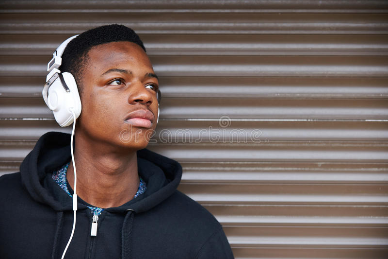 Teenage Boy Listening To Music In Urban Setting. Teenage Boy Listens To Music In Urban Setting royalty free stock photography