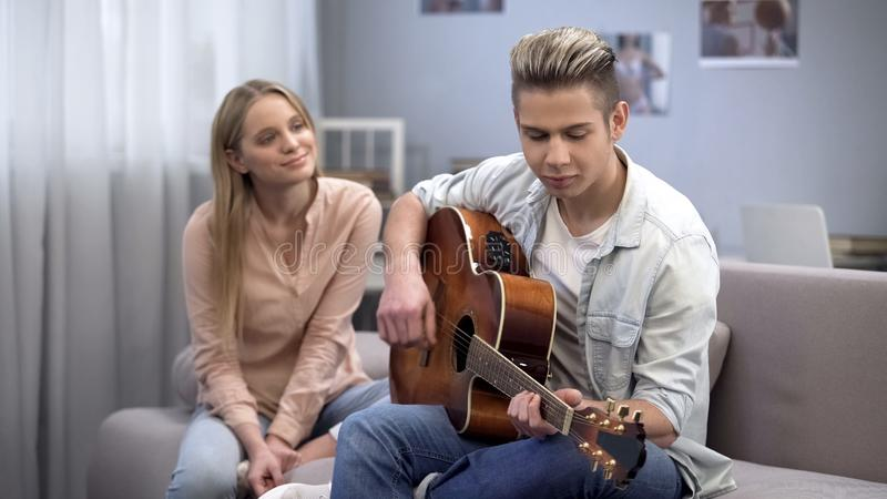 Teenage boy in love playing guitar to girlfriend conquering her heart, romance. Stock photo royalty free stock image
