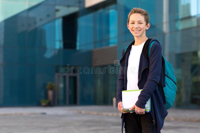 Teenage boy outdoor with books and backpack stock photography