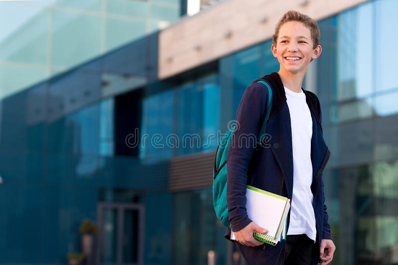 Teenage boy outdoor with books and backpack. Copy space royalty free stock photos