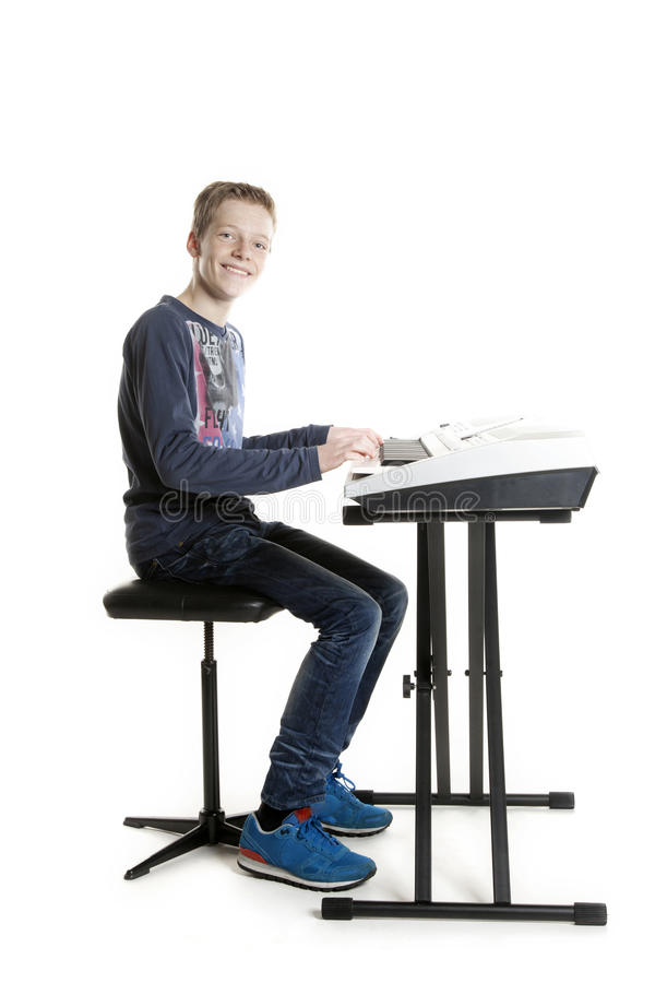 Teenage boy plays keyboard in studio. Teenage boy at keyboard in studio against white background stock photography