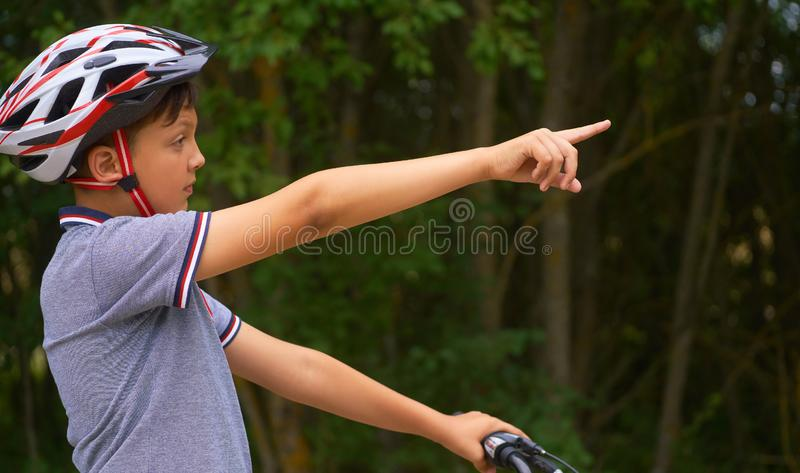 Teenage boy in protective helmet standing over my bike and showing the waypoints. royalty free stock photos