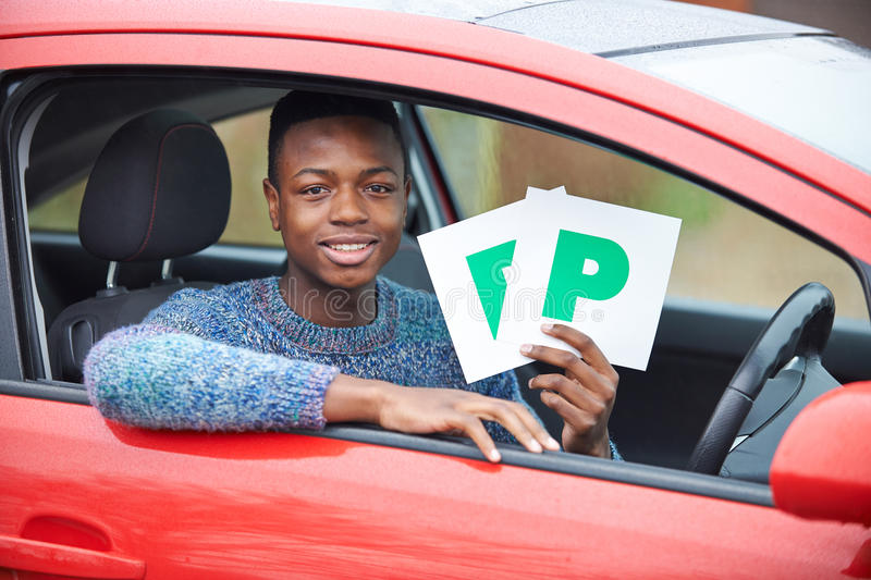 Teenage Boy Recently Passed Driving Test Holding P Plates. Teenager Recently Passed Driving Test Holding P Plates royalty free stock image
