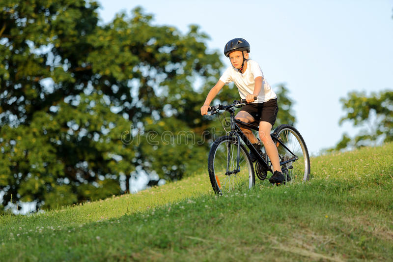 Teenage boy rides a bike from the hill in city park stock photo