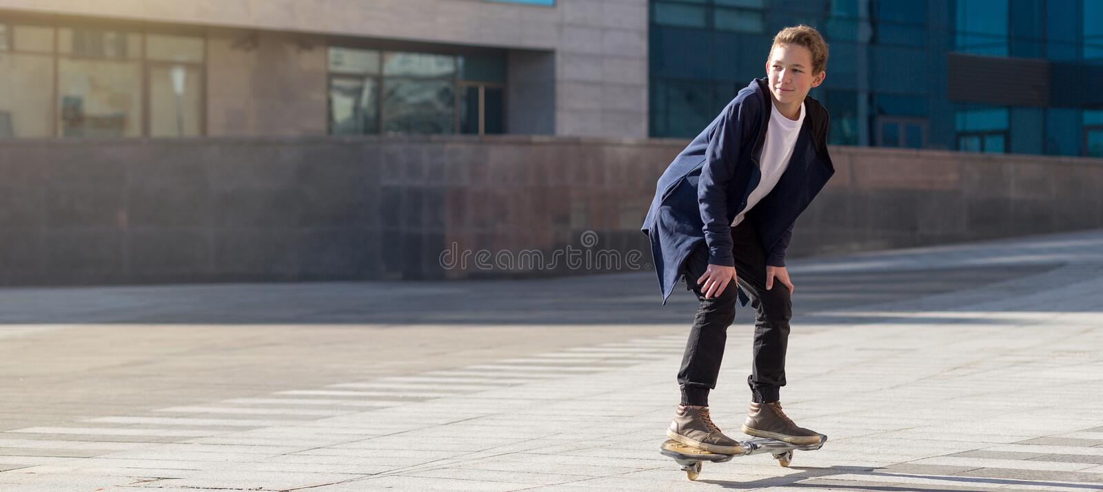 Teenage boy riding a scateboard on the boardwalk with copy space.  stock images