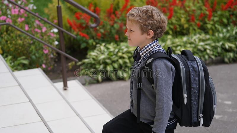 Little Caucasian curly boy in school uniform with backpack comes up on stairs. Teenage boy in school uniform with backpack standing on stairs. School yard in royalty free stock photo