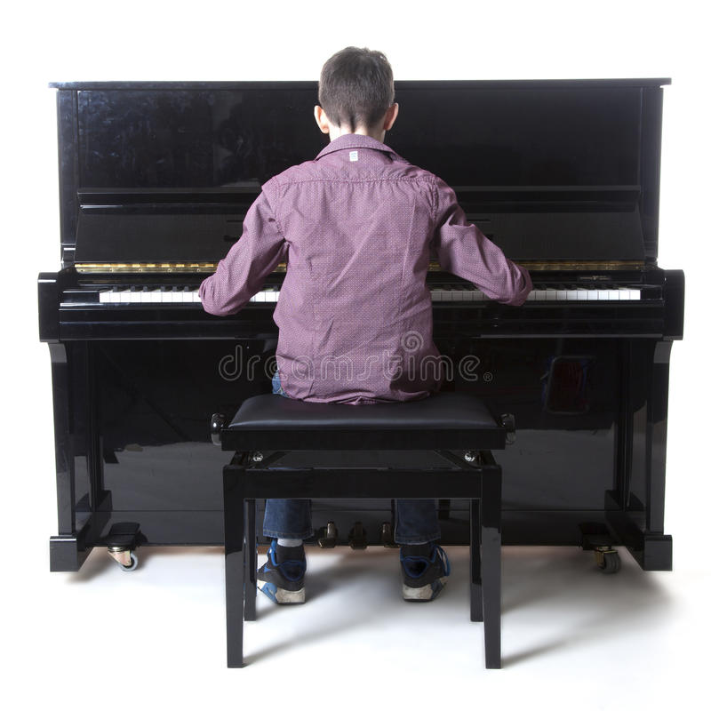 Teenage boy sits at upright piano in studio. With white background royalty free stock photo