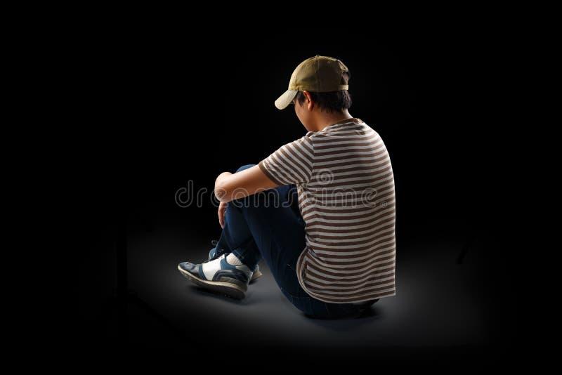 Teenage boy sitting alone. Isolated over black royalty free stock image