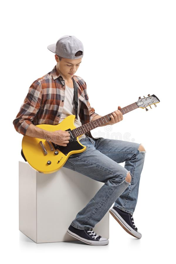 Free Teenage Boy Sitting On A Cube And Playing An Electric Guitar Stock Photography - 118329232