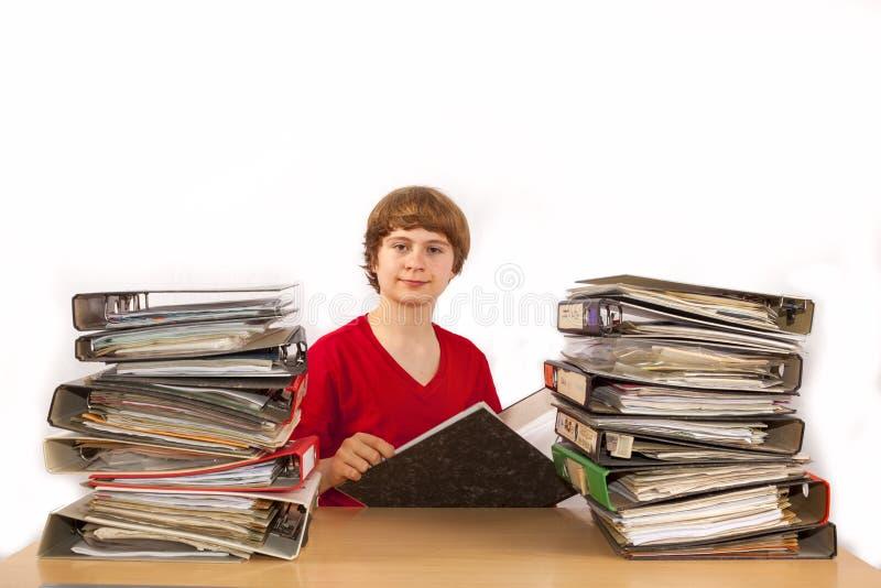 Teenage Boy sitzt an einem Schreibtisch mit vielen Ordnern und liest lizenzfreies stockfoto