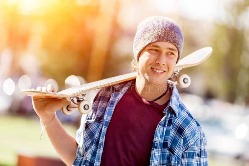 Teenage boy with skateboard standing outdoors. Teenage boy with skateboard standing in the park royalty free stock photo