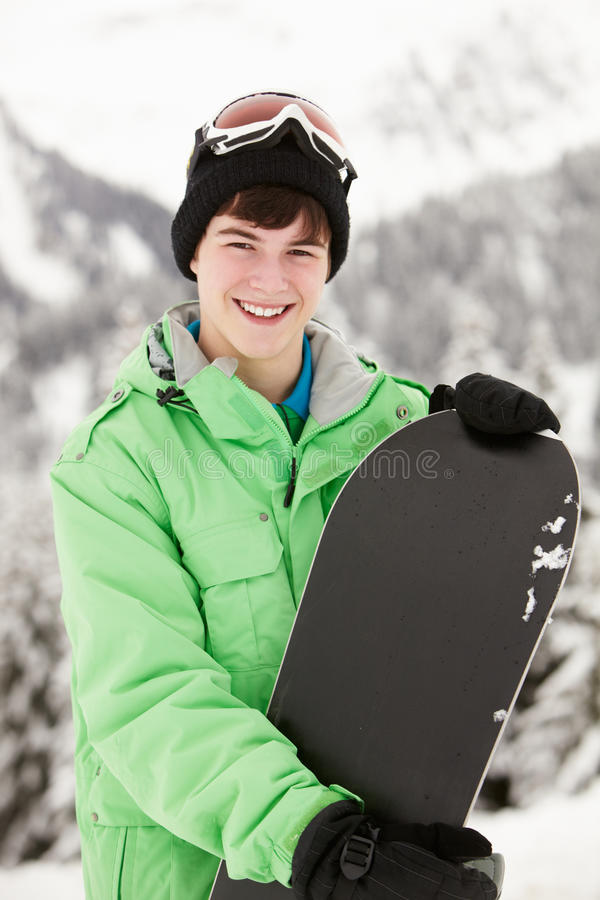 Teenage Boy With Snowboard On Ski Holiday stock photo