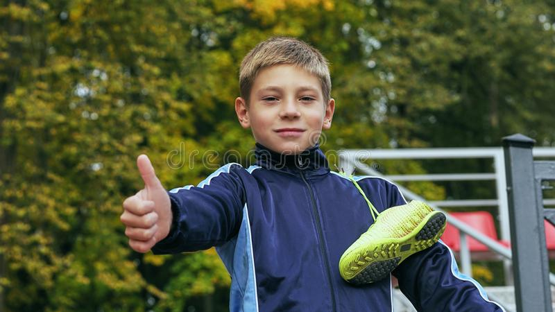 Smiling teenage boy showing thumbs up with a soccer ball in his hand and soccer boots on the shoulder against the. Teenage boy with a soccer ball in his handand stock photography