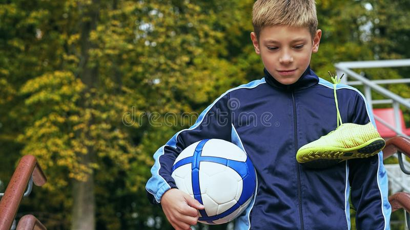 Smiling teenage boy with a soccer ball in his hand and soccer boots on the shoulder against the background of the. Teenage boy with a soccer ball in his handand royalty free stock photos