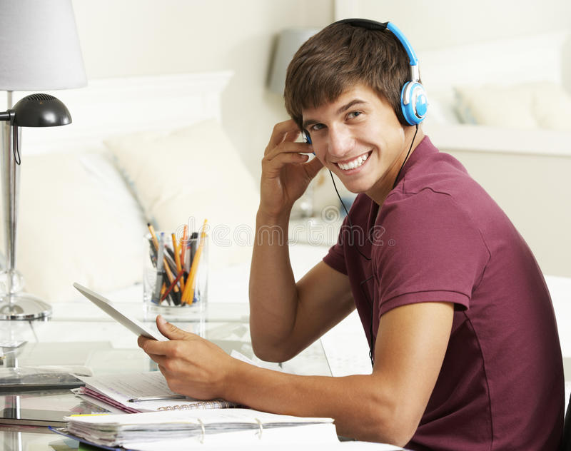 Teenage Boy Studying At Desk In Bedroom Using Digital Tablet stock image