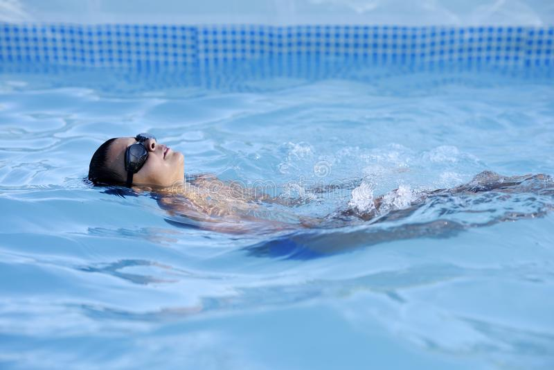 A teenage boy swimming in a swimming pool. Young boy swimming in a swimming pool royalty free stock photo
