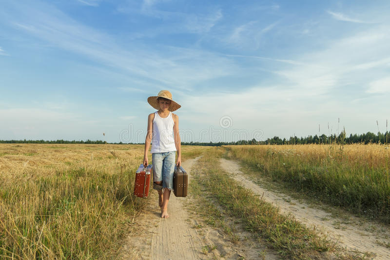 Teenage boy traveling by foot on country road stock images