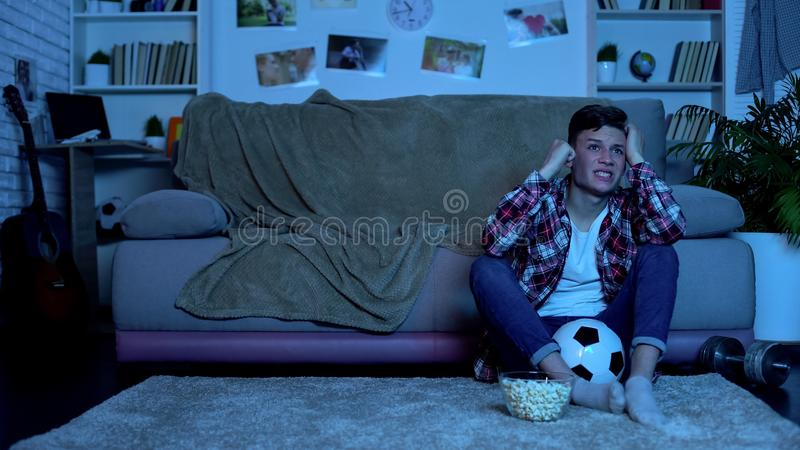 Teenage boy watching soccer game on tv at home, upset with result of match. Stock photo royalty free stock photos