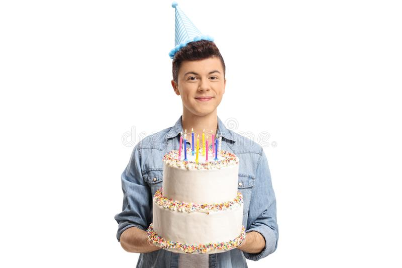 Teenage boy wearing a party hat and holding a cake stock images