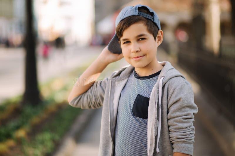 Teenage boy wears a cap. Stylish male outside royalty free stock image