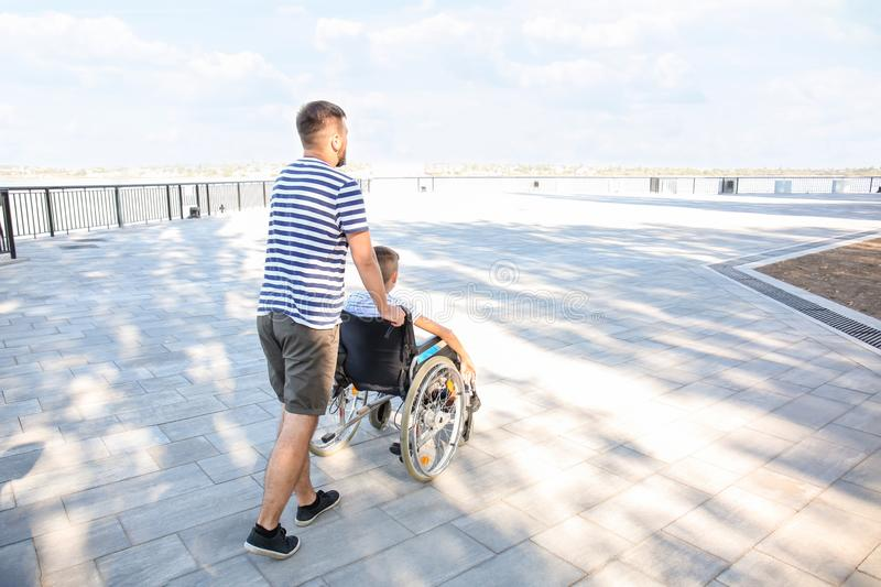 Teenage boy in wheelchair with his father walking outdoors royalty free stock photo