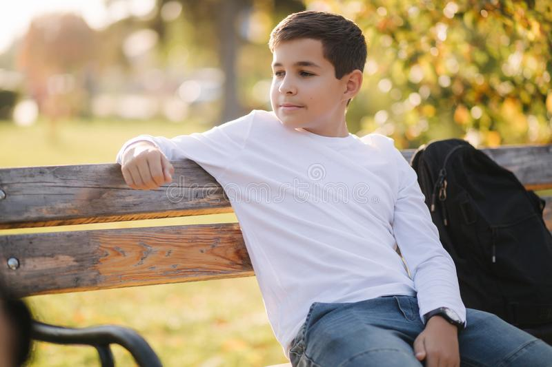 Teenage boy in white sweater sitting on the bench. Handsome school boy with backpack in autumn park stock image