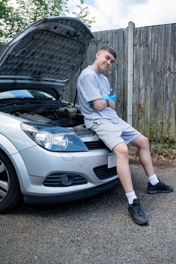 Teenage boy working on a car stock image