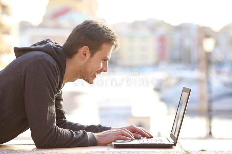 Teenage boy writing in a laptop on vacation royalty free stock images