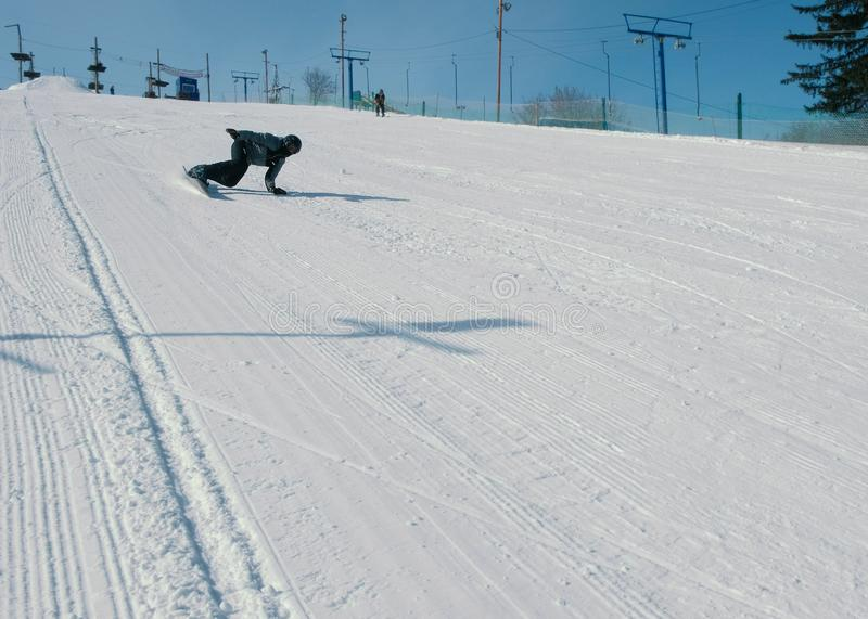 Teenage boy of 12 years sliding on a snowboard from snow descent next sky lift. Teenage boy of 12 years sliding on a snowboard from snow descent next sky lift stock photo