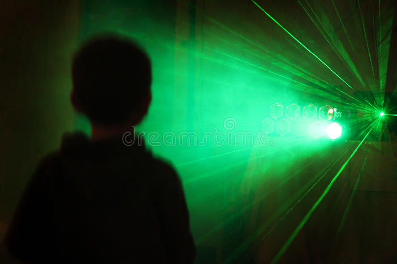 Teenage Boy. A young teen stands alone staring into and at a laser display at a party royalty free stock photos