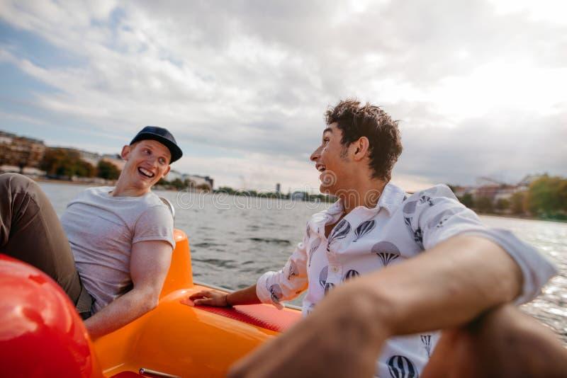 Teenage boys enjoying boating in the lake stock photo