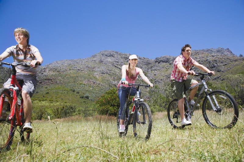 Teenage Boys And Girl Biking Outdoors royalty free stock photo