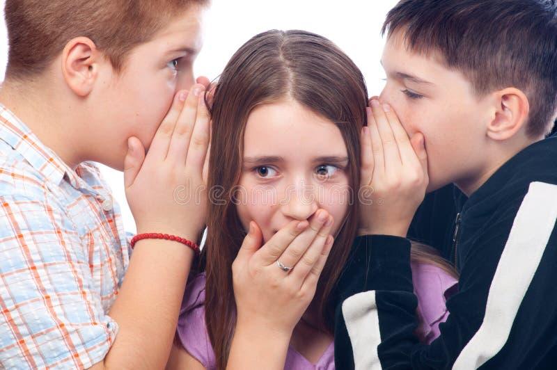 Teenage boys and girl gossiping stock photo