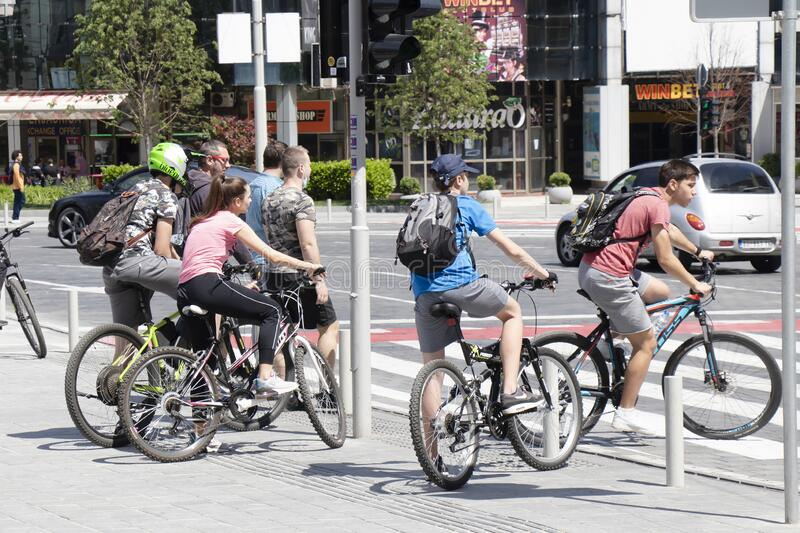 Teenage boys and girls riding bikes on city street,  at pedestrian crossroad royalty free stock image
