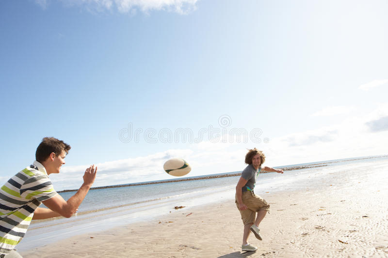Teenage Boys Playing Rugby On Beach Together Stock Photos