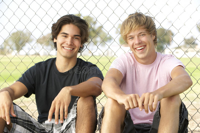Download Teenage Boys Sitting In Playground Stock Photo - Image: 12839220