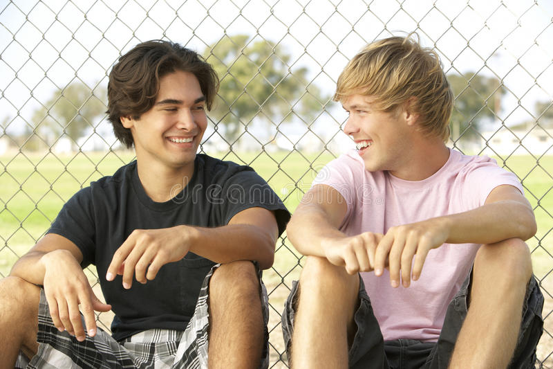 Teenage Boys Sitting In Playground royalty free stock image