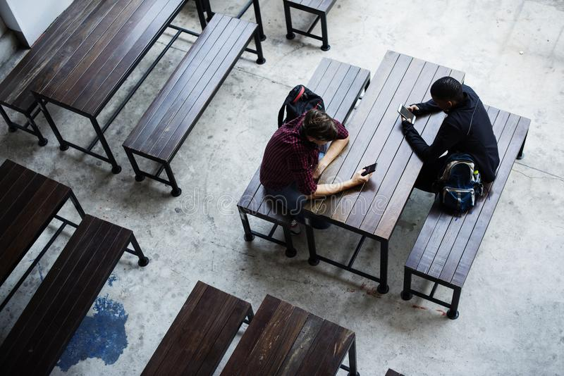 Teenage boys sitting together in a empty canteen stock photo