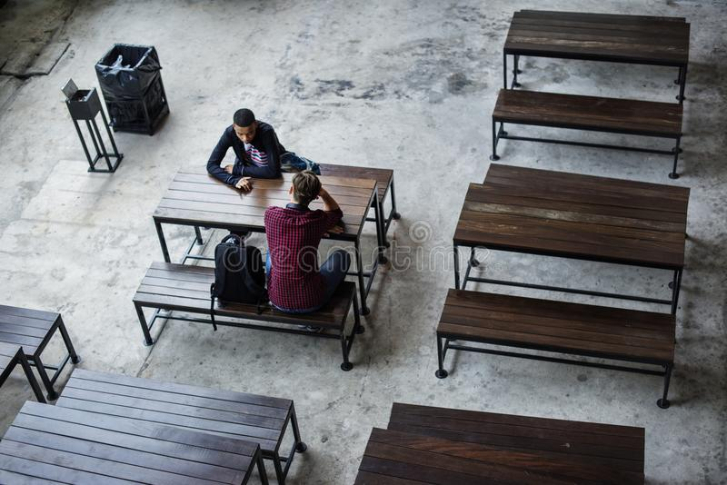 Teenage boys sitting together in a empty canteen stock photos
