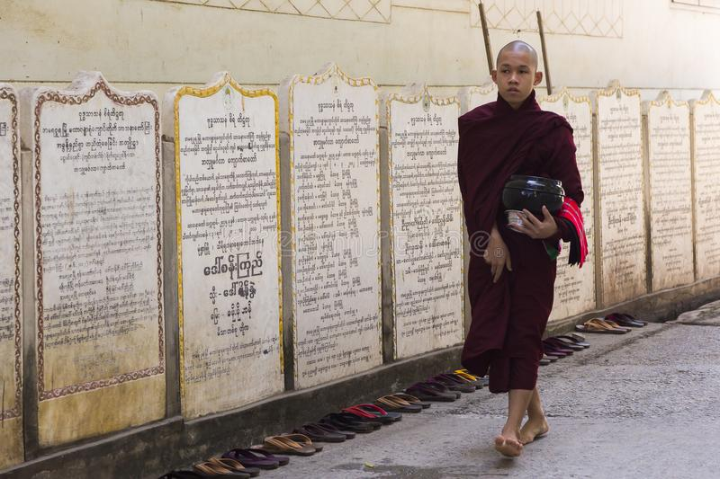 Teenage Burmese monk in dark purple robes holding bowl and walking barefoot royalty free stock photos
