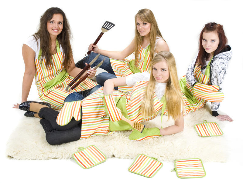 Teenage chefs. Four teenage girls in cooking costumes with grilling utensils ready to cook stock image