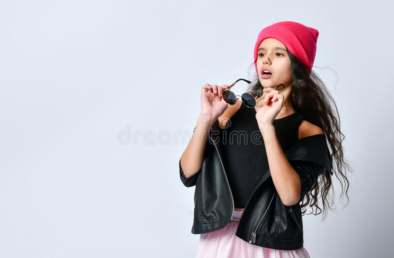 Teenage child in black leather jacket, skirt and pink hat. She is holding her sunglasses, posing isolated on white. Close up. Brunette teenage child in black royalty free stock photos
