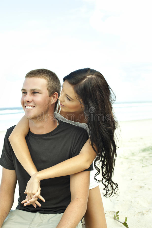 Teenage couple on beach stock photos