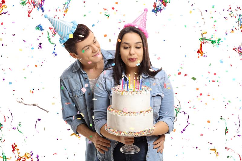 Teenage couple with a birthday cake and confetti streamers flyin. G around them isolated on white background royalty free stock photos