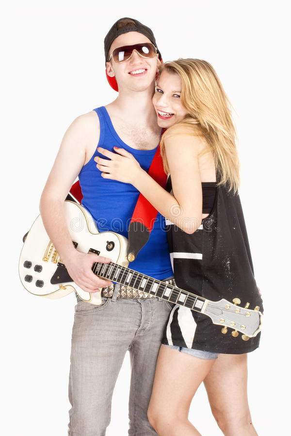 Teenage Couple - Girl Embracing her Boyfriend with Guitar royalty free stock image