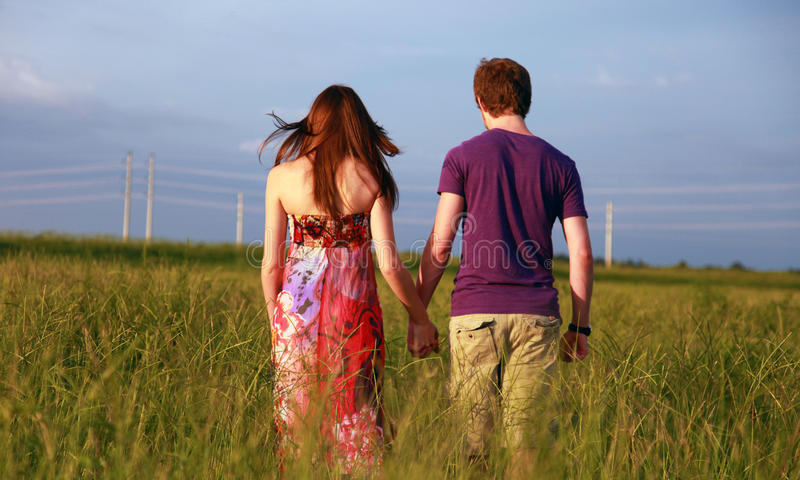 Teenage couple holding hands royalty free stock photography