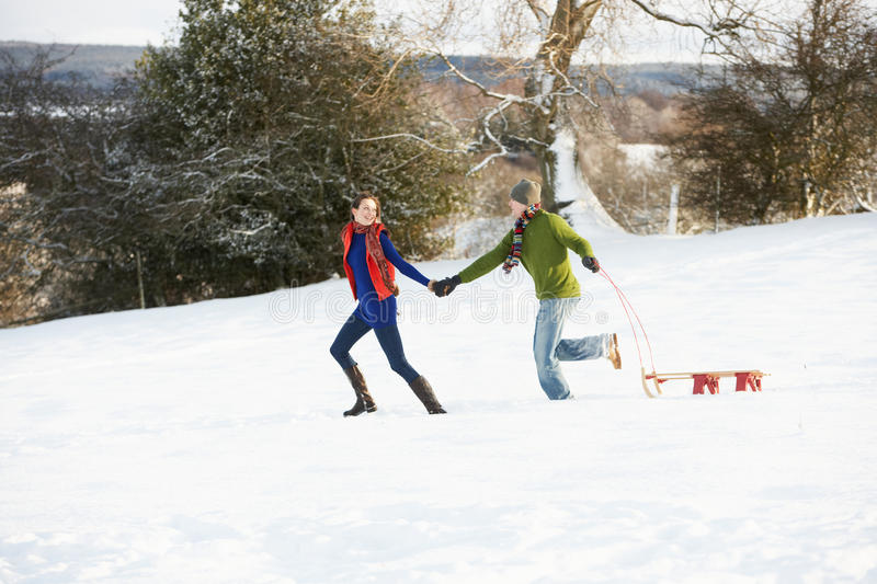 Download Teenage Couple Pulling Sledge Across Snowy Field Stock Photo - Image: 14188936