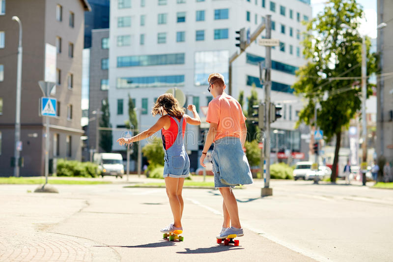 Teenage couple riding skateboards on city street. Summer, extreme sport and people concept - teenage couple riding short modern cruiser skateboards on city royalty free stock photos